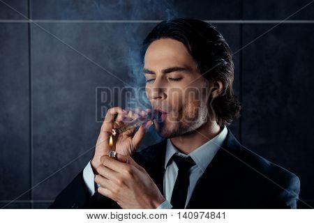 Closeup Portrait Of Brutal Young Man Lights A Cigar