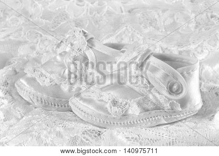 White baby booties on lace background