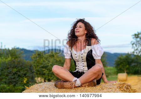 Pretty Woman Sitting On A Hay Bale Daydreaming
