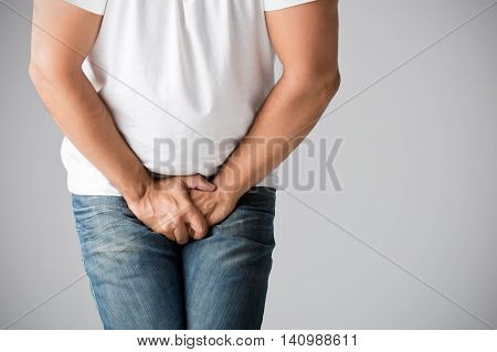 Close up of a man with hands holding his crotch isolated in grey