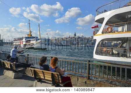 Istanbul Turkey - July 26 2016: Galata Bridge Galata Tower Ferry Istanbul Views. This is a great place to see the colors of Istanbul at . Interesting to see the fishermen on the bridge with the Galata tower in the background. There are lots of restaurants