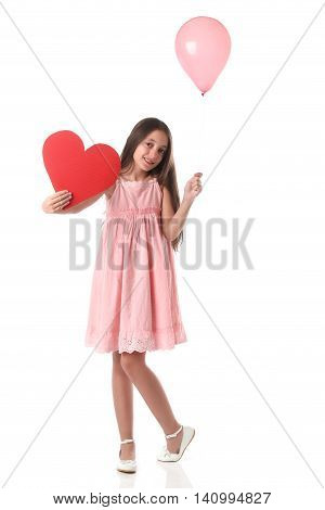 Lovely girl holding a red heart shape and a pink balloon. Over white background. Love concept