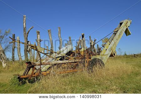 An old one row corn picker run by a power takeoff sits in the woods and weeds,