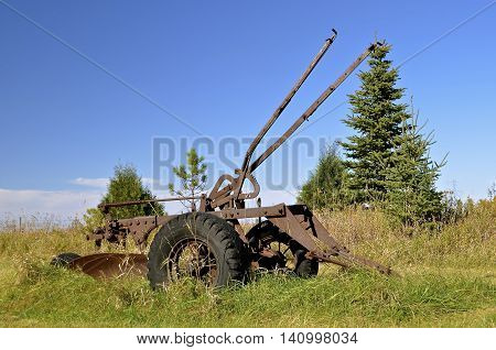 Parked in the grass is a vintage three bottom trip plow which would unhook if hitting a large rock when plowing a field.
