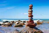 Concept of harmony and balance. Rock Zen on the storm background. Balance and poise stones against the sea poster