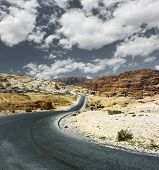 Asphalt road in mountains and blue sky with clouds
