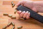 Woman Loading 9mm Ammunition in High Capacity Handgun Magazine on wood Surface poster