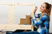 Woman assembling wooden furniture using hex key. DIY enthusiast. Young girl doing home improvement. poster