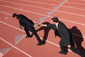 Businessmen passing the baton in a track relay poster