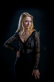 Beautiful Russian blonde girl on a black background in a dark guipure dress