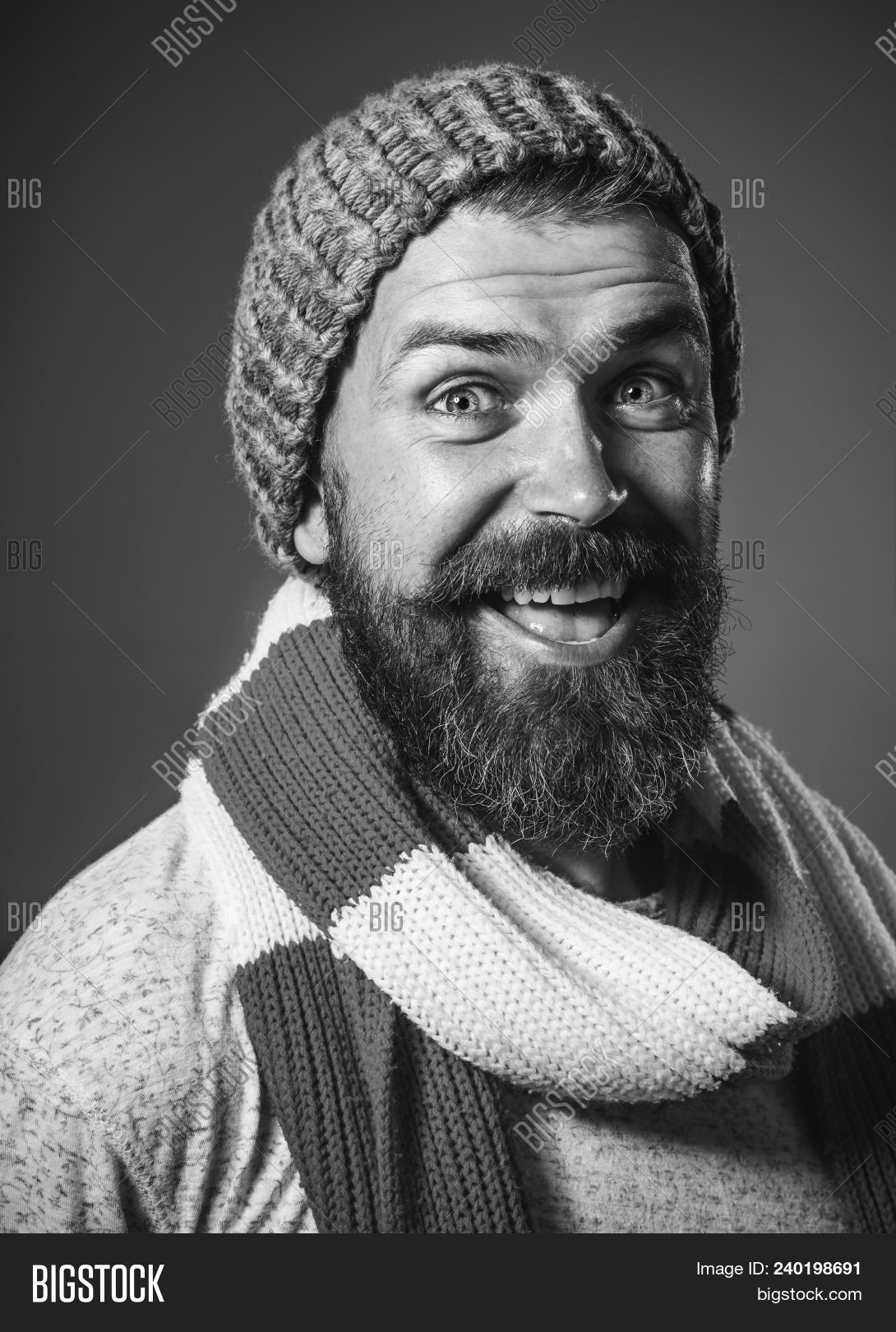 1d49f6bd04d Fashionable handsome man with scarf and hat. Smiling attractive bearded man  in warm knitted hat and scarf. Closeup portrait. Black and white.