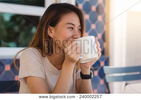 Portrait Of Happy Young Asian Business Woman With Mug In Hands Drinking Coffee In The Morning At Caf