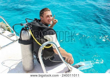 A Scuba Diver Before Diving. Guy In Diving Outfit Preparing To Dive Into The Ocean.