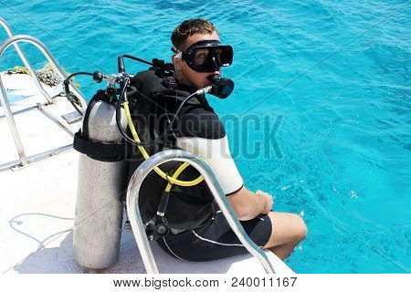 A Man In A Wet Suit, With An Aqualung, Mask And A Balloon. A Diver In Diving Gear Is Preparing To Di