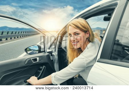 Beautiful Blonde Girl Driving A Car On The Highway. The Woman Opens The Car Door. Invitation To Trav