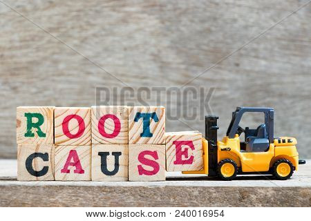 Toy Forklift Hold Letter Block E To Complete Word Root Cause On Wood Background