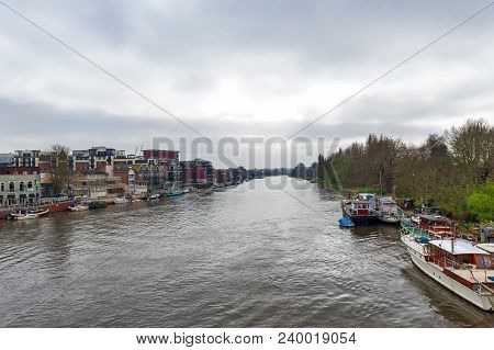 Kingston Upon Thames, United Kingdom - April 2018: The River Thames Flowing Pass The City Of Kingsto