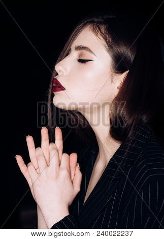 Pray And Hope Concept. Girl On Calm Face With Closed Eyes In Black Jacket, Black Background. Woman W