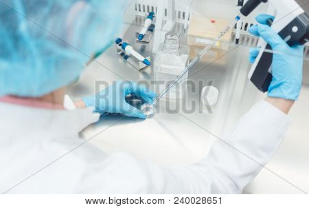Scientist in lab conducting biotechnological experiment using pipette and petri dish