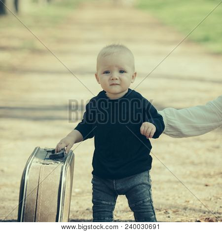Small Boy Carry Retro Suitcase On Natural Landscape. Child Travel For Vacation With Bag With Mothers
