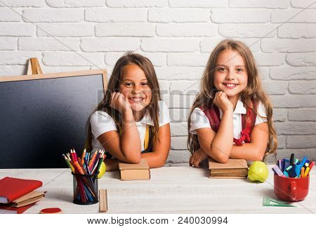 Back To School And Home Schooling. Happy School Kids At Lesson In September 1. Little Girls Eat Appl