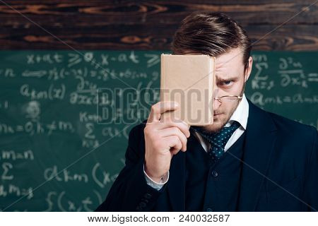 Young Man In Suit Covering His Face With Book. Closeup Portrait Of Young Blond Aristocrat With Styli