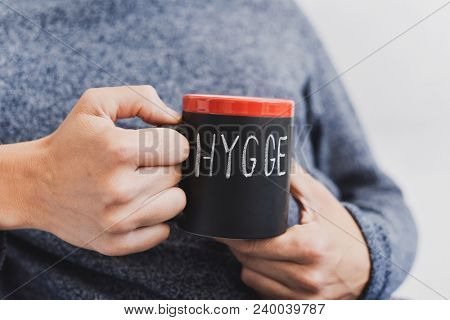 closeup of a young man sitting comfortably with a cup of coffee in his hand with the word hygge written in it, a danish and norwegian word for comfort or enjoy, which can be a whole philosophy of life