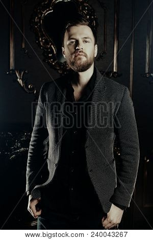 Portrait of a well-dressed imposing man in elegant suit posing in apartments with luxurious classic interior. Men's beauty, fashion.