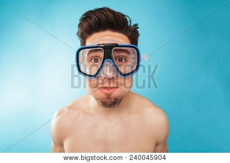 Portrait of a smiling young man in swim mask looking at camera over blue background