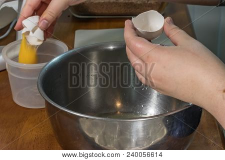 Droping Separated Egg Yolk Into A Nearby Tupperware Container
