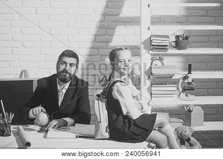 Back To School And First School Day Concept. Family Sits By Desk With School Supplies. Schoolgirl An