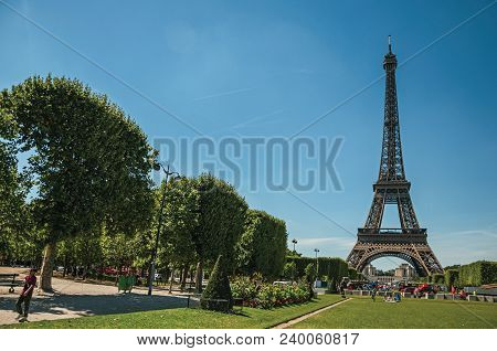 Paris, France - July 07, 2017. People, Greenery And Eiffel Tower With Sunny Blue Sky In Paris. Known