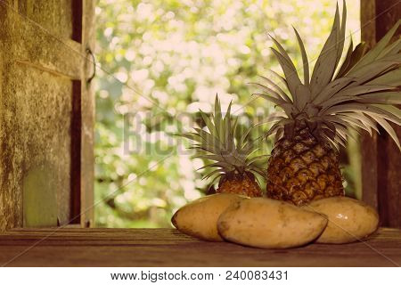 Pineapple With Ripe Mango On Wooden Table In Country Kitchen On Background Of Garden Behind Country