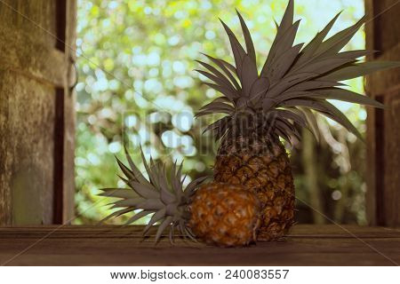 Pineapple On Wooden Table In Country Kitchen On Background Of Garden Behind Country House.