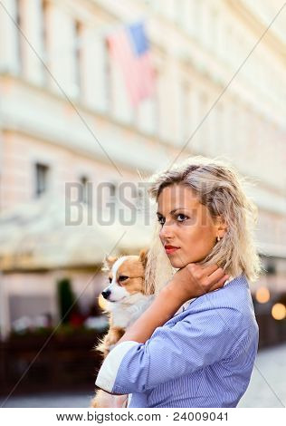 young blond woman with chihuahua in downtown. poster