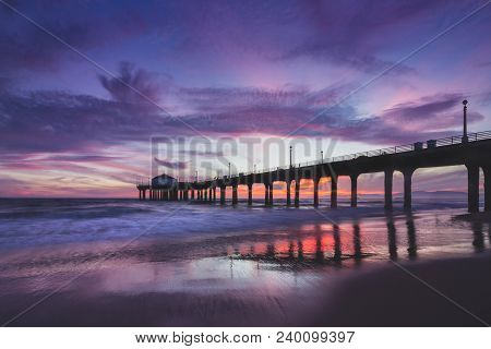 Long-exposure Shot Of Colorful Sky And Clouds Over Manhattan Beach Pier At Sunset With Smooth Waves