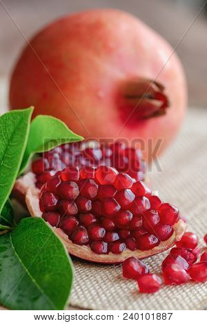 Sweet And Juicy Indian Red Pomegranate On Wood Table. Ripe Red Pomegranate In Close Up View Copy Spa