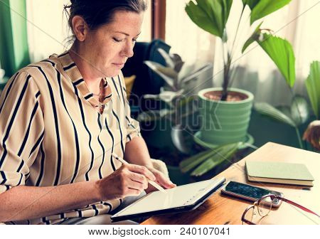 Caucasian woman writing to do list on tablet
