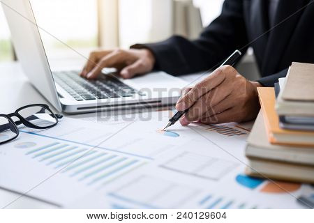 Female Accountant Calculations And Analyzing Financial Graph Data With Calculator And Laptop Busines