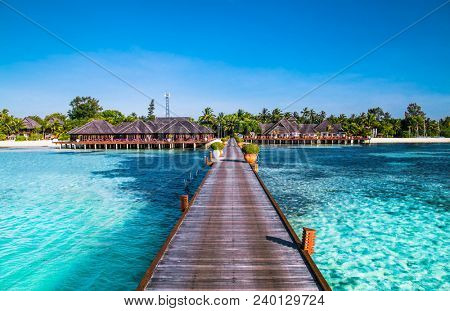 Tropical travel destinations with Maldives island and wooden wharf, exotic vacation