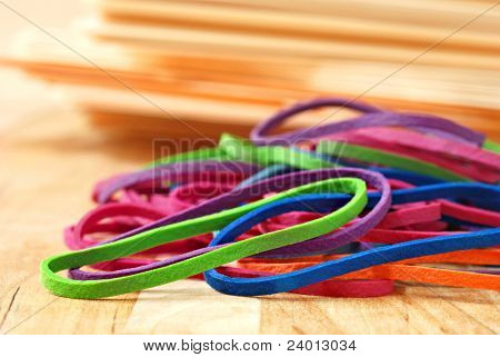 Brightly colored rubber bands with stack of manilla folders in soft focus in background.  Macro with extremely shallow dof.