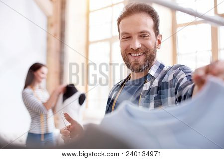Fashion look. Low angle of cheerful male stylist choosing garment while looking down poster