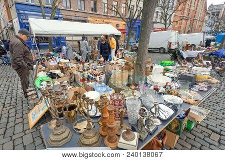 Brussels, Belgium - Apr 3: Buyers On Flea Market With Old Metal Candlesticks, Bargains, Antique Stuf
