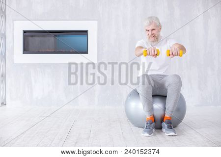 Making Arms Stronger. Upbeat Elderly Man Sitting On The Yoga Ball And Holding A Pair Of Dumbbells Wh