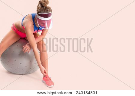 Fitness Woman In Sportswear Sitting On Gymnastic Ball, Perfect Sporty Body On Pastel Background