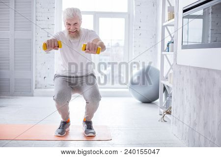 Upbeat Mood. Joyful Senior Man Doing Squats And Posing For The Camera, Smiling Brightly, While Holdi