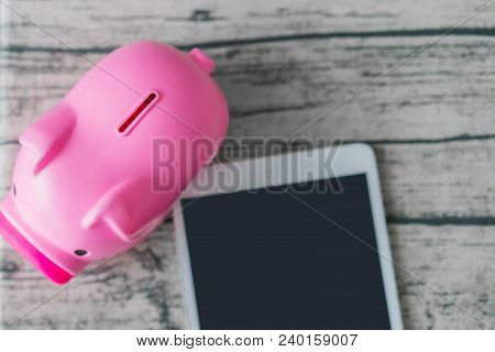 Piggy Bank And Tablet Computer On The Table.