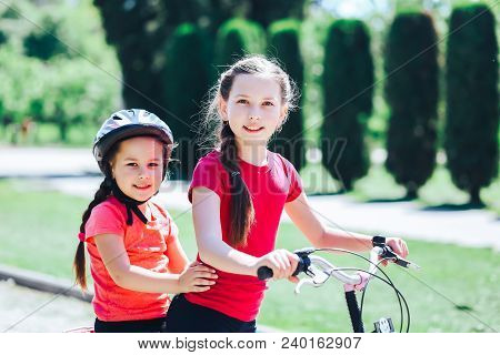 The Older Sister Bicycles Her Younger Sister.
