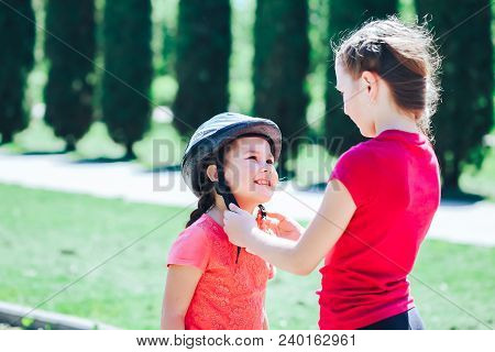 Older Sister Wears Protective Bicycle Helmet To Younger Sister