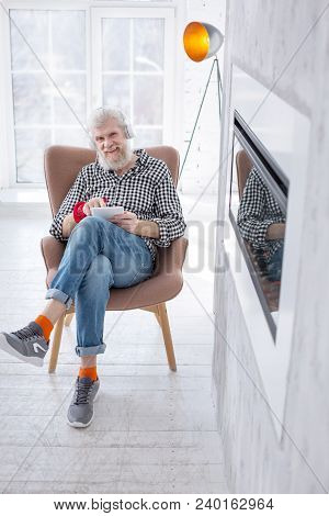 Favorite Content. Upbeat Elderly Man Sitting In An Armchair Comfortably And Smiling At The Camera Wh